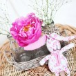 Stock Photo: Pink peony in vase and pink toy rabbit on wooden table