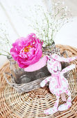 Pink peony in vase and pink toy rabbit on wooden table — Stock Photo