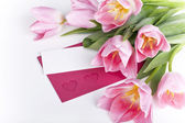 A bunch of pink tulips with a blank card for greetings — Stock Photo