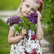 The little girl with a lilac bouquet in a garden — Stock Photo #25784463