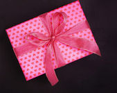 Pink gift box in heart pattern on black background — Stock Photo