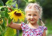 Little girl and sunflower — Stock Photo