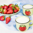 Strawberries on a plate and milk in ceramic cups on blue napkin — Stock Photo