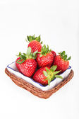 Strawberries in a basket on white wooden background — Foto de Stock