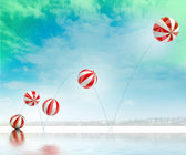 Five jumping white red striped inflatable balls on beach with sea — Stock Photo