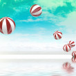 Six jumping white red striped inflatable balls on green blue clo — Stock Photo