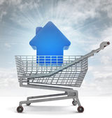 Real estate house in shoping cart with sky flare — Stock Photo