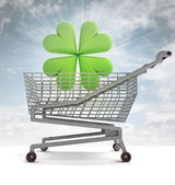 Shoping cart with green cloverleaf and sky flare — Stock Photo