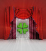 Red curtain scene with green cloverleaf and flare — Stock Photo