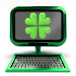 Photo: Green metallic computer with lucky cloverleaf on screen concept isolated