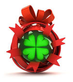 Opened red ribbon gift sphere with green cloverleaf inside — Stock Photo