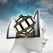 Movie tape fun coming out or in human head with sky background — Stock Photo #37838499