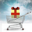 Bought of gift cake in shopping cart with sky — Stock Photo