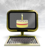 Golden metallic computer with cake celebration with background flare — Stock Photo