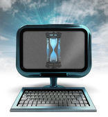 Blue metallic computer with sand glass with background flare — Stock Photo