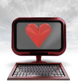 Red metallic computer with love symbol with background flare — Stock Photo