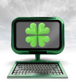 Green metallic computer with lucky cloverleaf with background flare — Stock Photo