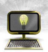 Yellow metallic computer with shiny bulb with background flare — Stock Photo
