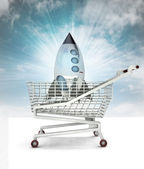Bought space rocket toy in shopping cart with sky — Stock Photo