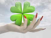 Green lucky cloverleaf in women hand render — Stock Photo