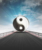 Yin and yang on motorway leading to harmony with sky flare — Stock Photo