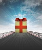 Christmas gift on motorway leading to xmas celebration with sky flare — Stock Photo