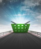Shopping basket on motorway track leading to supermarket with sky flare — Stock Photo