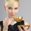Blond woman holding cup of coffee — Stock Photo