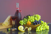 Bottle of red vine with fruits — Stock Photo