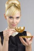 Mujer rubia sosteniendo la taza de café — Foto de Stock