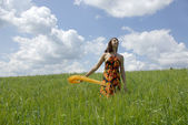 Beautiful woman in green grass field and cloud sky — Stock Photo