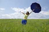 Beautiful woman holding blue umbrella in green grass field and cloud sky — Stock Photo