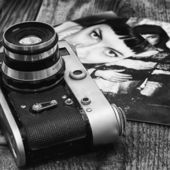 Old film camera on a background of old girls photos — Stock Photo