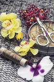 Composition with sewing tools and floral decorations — Stock Photo