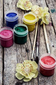 Jars of water color paints and brushes — Stock Photo