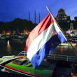 Stock Photo: Dutch flag flying on steamboat at night