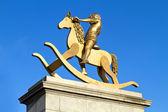 Gouden standbeeld van jonge kind op schommelpaard — Stockfoto