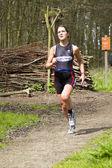 Jolien janssen corriendo la parte boscosa del curso — Foto de Stock