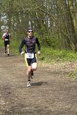 Běžci v zalesněné části kurzu — Stock fotografie