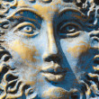 Blue and gold weathered sun face — Stock Photo #13489134