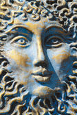 Blue and gold weathered sun face — Stock Photo