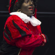 Zwarte Piet entertaining children on Saint Nicolas parade - Stock Photo