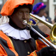 Zwarte Piet playing trombone. He is a helper of Dutch Saint Nico — Stock Photo