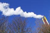 青い空を背景に煙を発光煙突 — ストック写真