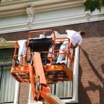 Painter on aerial access platform — Stock Photo
