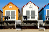 Yellow blue and white beach houses — Stock Photo