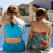 Two sisters stitting by the pool — Stock Photo