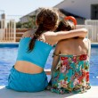 Two girls ebracing by the pool - Stock Photo