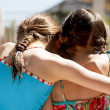 Two sisters ebracing by the pool - Stock Photo