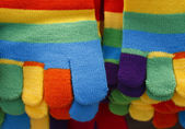 Knitted striped winter gloves in bright colors — Stock Photo